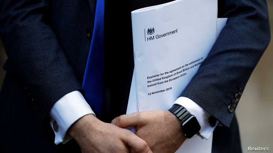 Conservative Party politician Steve Baker holds a Brexit document as British Member of Parliament, Jacob Rees-Mogg, speaks from St Stephen's Entrance at the Houses of Parliament, in London, Britain Nov. 15, 2018.