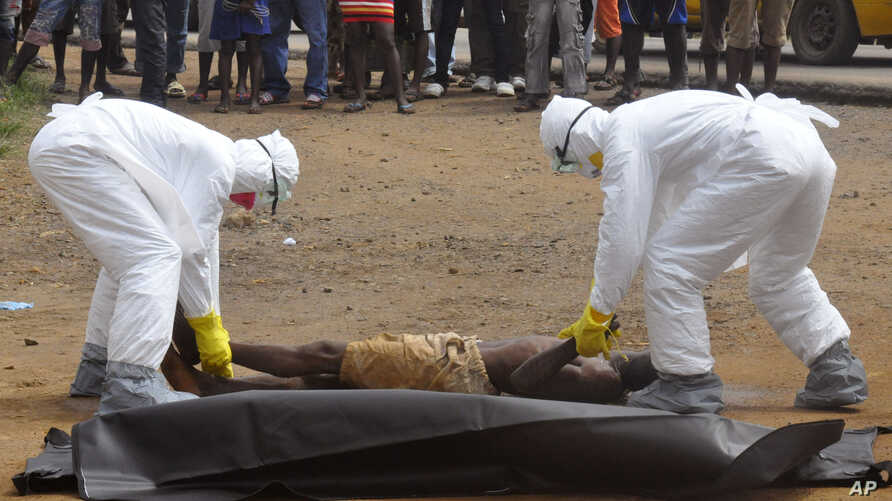 FILE - Health workers place the body of a man, whom they suspect of dying of the Ebola virus, inside a plastic body bag as a small crowd watches in Monrovia, Liberia, Sept. 4, 2014.