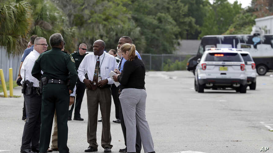 Authorities confer near the scene of a shooting where they said there were multiple fatalities in an industrial area near Orlando, Fla., June 5, 2017.