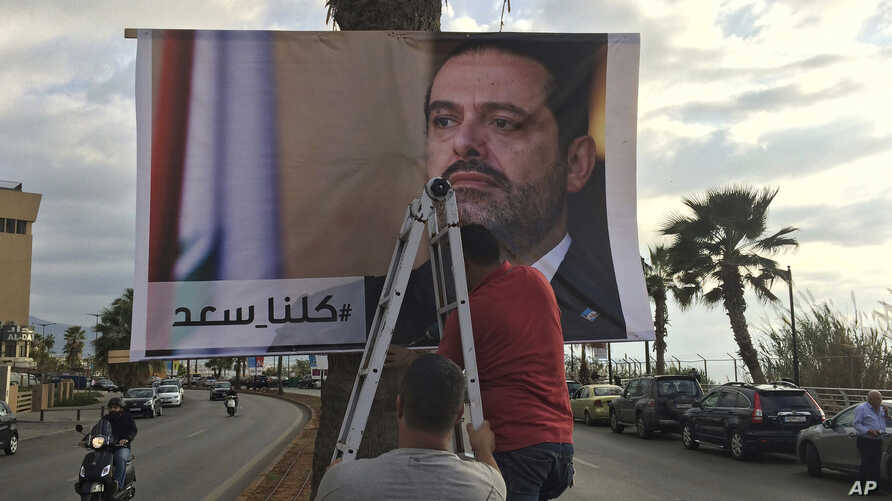 "Workers hang a poster of outgoing Prime Minister Saad al-Hariri with Arabic words that read ""We are all Saad,"" on a seaside street in Beirut, Lebanon, Nov. 9, 2017. Hezbollah has called on Saudi Arabia to stay out of Lebanese affairs, saying the resi"