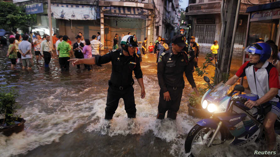 FILE - A policeman directs traffic as residents move through the floods as it advances into central Bangkok.
