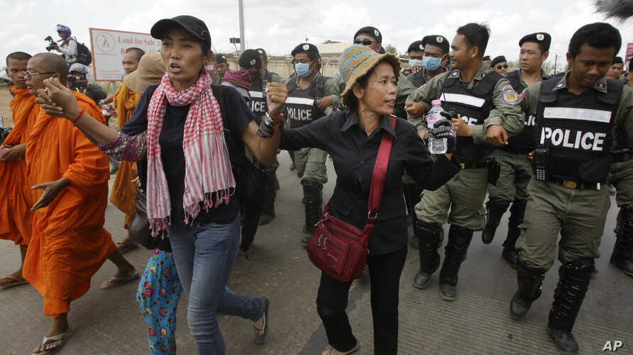 Cambodian civil rights supporters are forcibly directed by riot police as they march in protest of charges brought against local rights activists near  Prey Sar prison, outside Phnom Penh, Cambodia, Monday, May 9, 2016. (AP Photo/Heng Sinith)