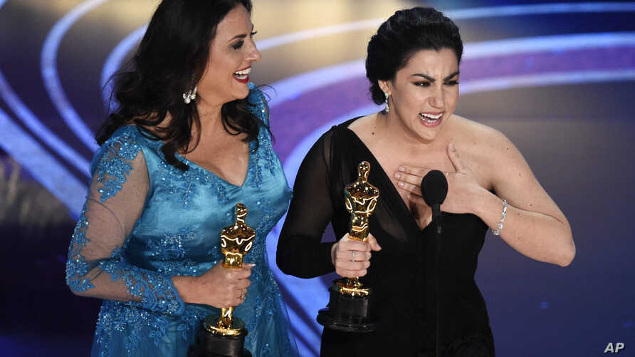 """Rayka Zehtabchi, right, and Melissa Berton accept the award for best documentary short subject for """"Period. End of Sentence."""" at the Oscars at the Dolby Theatre in Los Angeles, Feb. 24, 2019."""