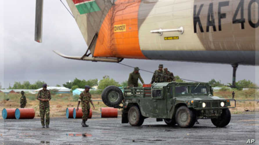 Kenyan military personnel prepare to fuel a supplies helicopter at the Garrisa airstrip near the Somali-Kenya border, October 18, 2011.