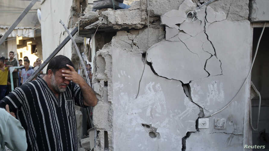 A Palestinian man reacts as he stands next to the wreckage of a house, which witnesses said was destroyed in an Israeli air strike that killed at least nine members from the al-Ghol family, in Rafah in the southern Gaza Strip, August 3, 2014.