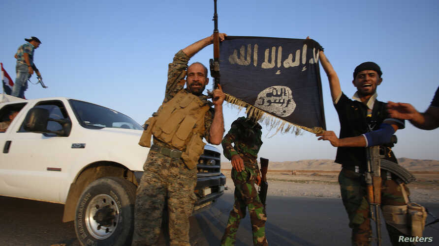 Iraqi Shiite militia fighters hold the Islamic State flag as they celebrate after breaking the siege of Amerli by Islamic State militants, Sept. 1, 2014.