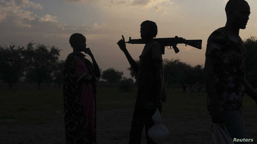 An armed man and a woman from the Luo Nuer tribe talk in Yuai Uror county, South Sudan, July 24, 2013.