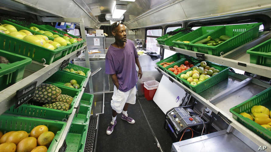 Jock Riggins looks over the fresh fruits and vegetables on the Fresh Stop bus, a mobile market, in Eatonville, Florida, Jul. 15, 2015..