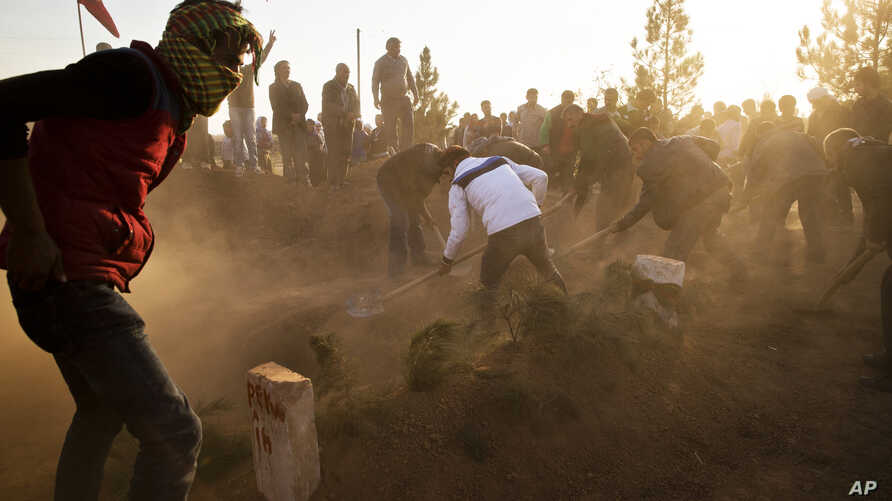 Kurds cover the grave of Ahmed Mustafa, a People's Protection Units (YPG) fighter, who died after being injured while fighting the Islamic State forces in the Syrian city of Kobani, during his funeral in Suruc, on the Turkey-Syria border, Nov. 12, 20