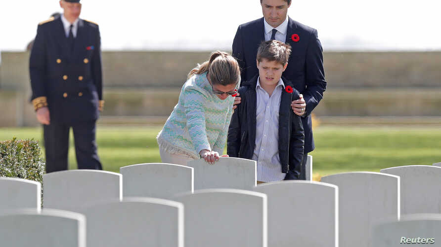 Canadian Prime Minister Justin Trudeau, his wife Sophie Gregoire and son Xavier pay their respects at the tombstone of J.R. Gregoire, an ancestor who died during fighting in WWII, during their visit to the Canadian War Cemetery in Beny-sur-Mer, Franc