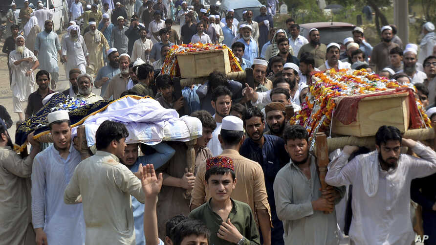 People carry the coffins of the victims of a suicide bombing at an election rally for burial in Peshawar, Pakistan, July 11, 2018.