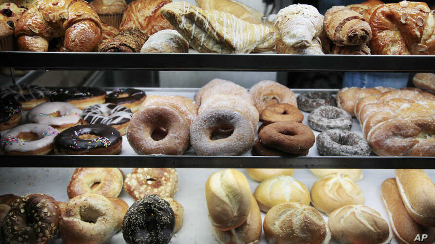 FILE - A selection of donuts, bagels, rolls, croissants, turnovers and sticky buns are displayed in a New York coffee cart, April 10, 2012.