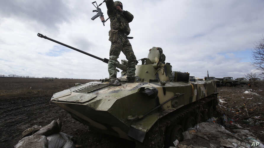 A Ukrainian soldier stands atop an armored vehicle at a military camp near the village of Michurino, Ukraine, March 17, 2014.