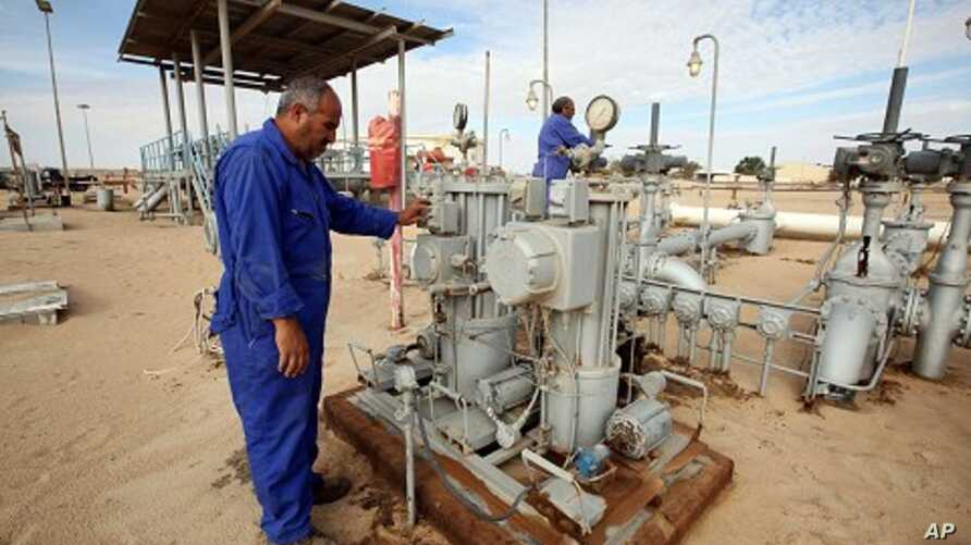 Workers check pipes and valves at Amaal oil field in eastern Libya, October 7, 2011.