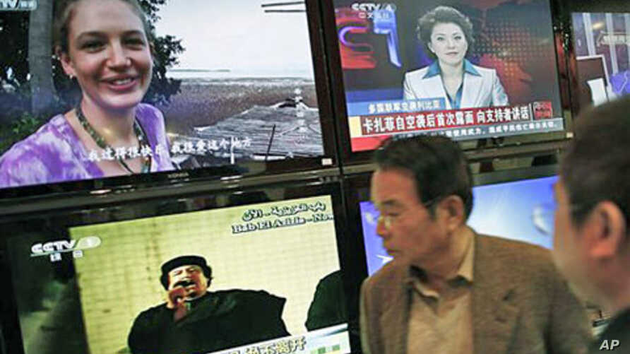 Visitors watch TV screens broadcasting news of Libyan leader Moammar Gadhafi speaking to his supporters, bottom left, during the China Content Broadcasting Network Expo in Beijing, March 23, 2011 (file photo)
