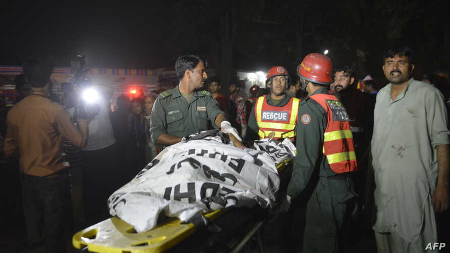 Pakistani rescuers use a stretcher to shift a body from a bomb blast site in Lahore on March 27, 2016.
