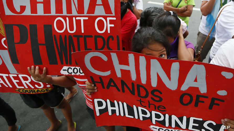 Protesters display placards during a rally at the Chinese consulate in the financial district of Makati city, east of Manila, Philippines, Nov. 12, 2015.
