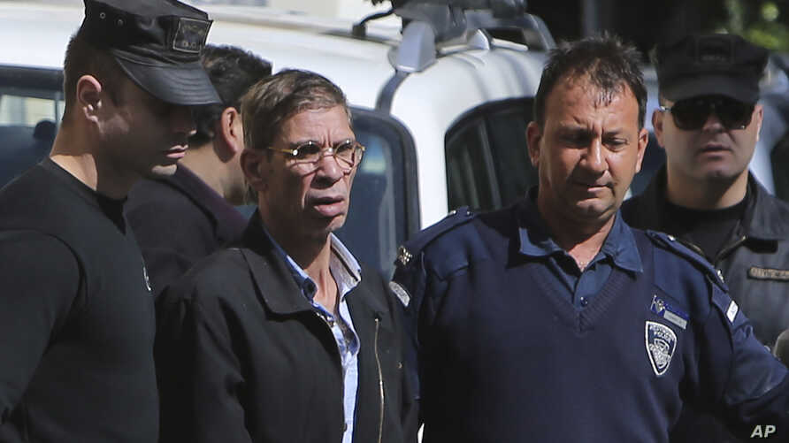 EgyptAir plane hijacking suspect Seif Eddin Mustafa, second left, is escorted by Cyprus police officers as he leaves a court after a remand hearing as authorities investigate him on charges including hijacking, illegal possession of explosives and ab...