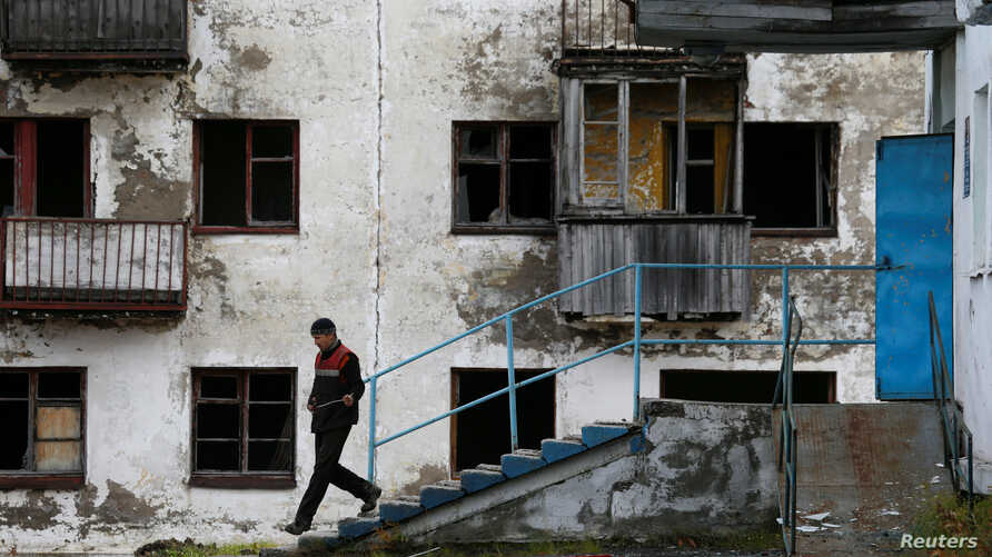 FILE - A laborer walks downstairs as he leaves a gym of a local school in Zapolyarny settlement outside the far northern city of Vorkuta, Russia, Sept. 17, 2018.