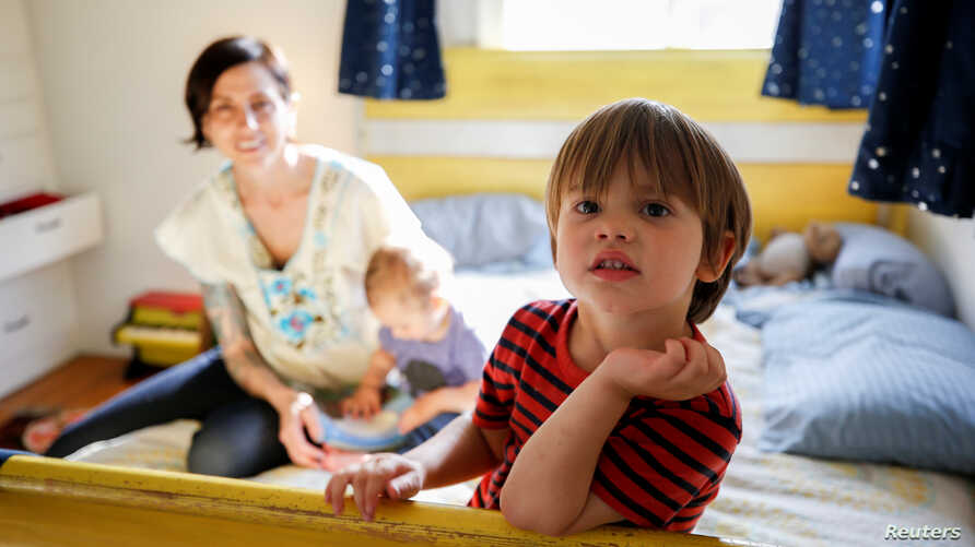 Three-year-old Wyatt Gries, right, sits on his bed inside his bedroom while his mother, Amanda Gries, holds his brother, Eli, in the Del Rey neighborhood of Los Angeles, California, April 4, 2017.