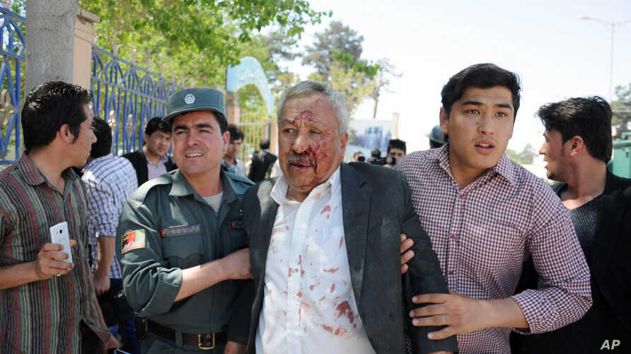 A wounded man is assisted after gunmen stormed a government compound in Mazar-e-sharif, north of Kabul, Afghanistan, April, 9, 2015.