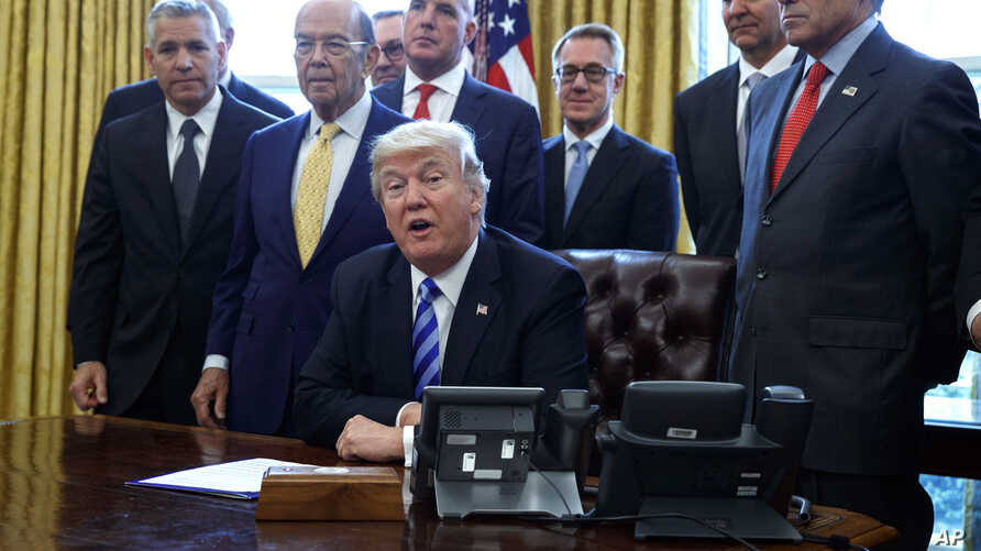 FILE - In this March 24, 2017, photo, President Donald Trump announces the approval of a permit to build the Keystone XL pipeline, clearing the way for the $8 billion project in the Oval Office of the White House in Washington. From left are, TransCa