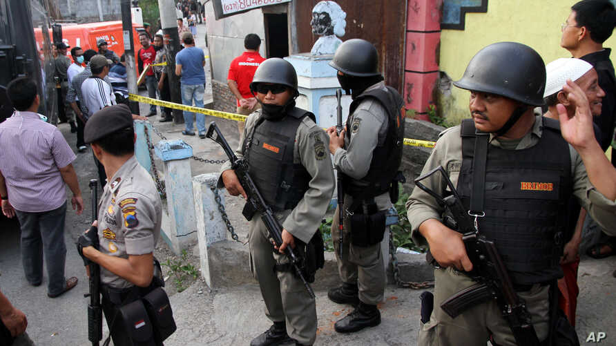 Indonesian police officers stand guard outside a building after a raid in Solo, Central Java, Indonesia, Saturday, Oct. 27, 2012.