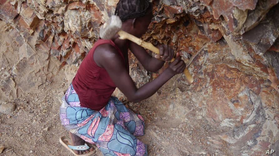 A woman rock-crusher hits rocks with a hammer in a quarry in Maroua, Cameroon, June 16, 2016.