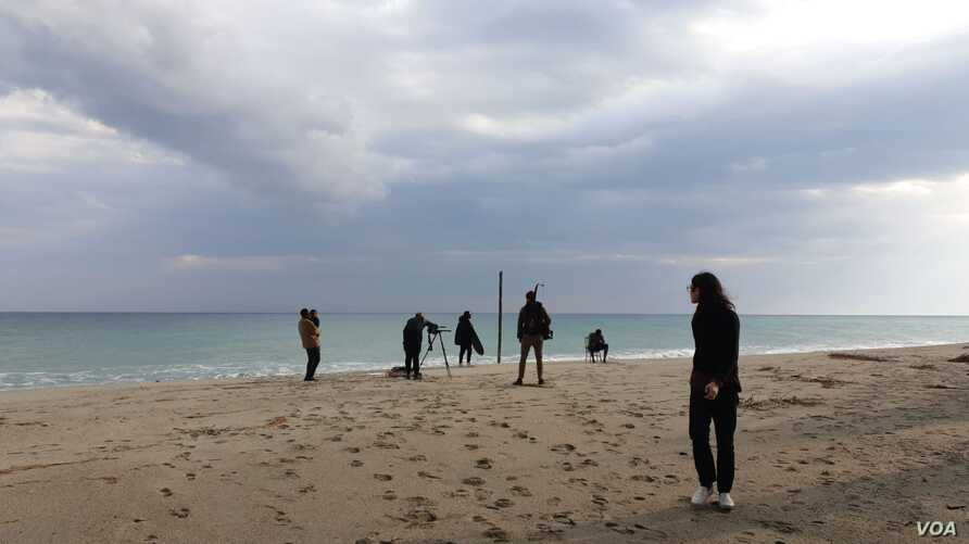 Team shooting with migrants on Stignano beach, Calabria, Italy.