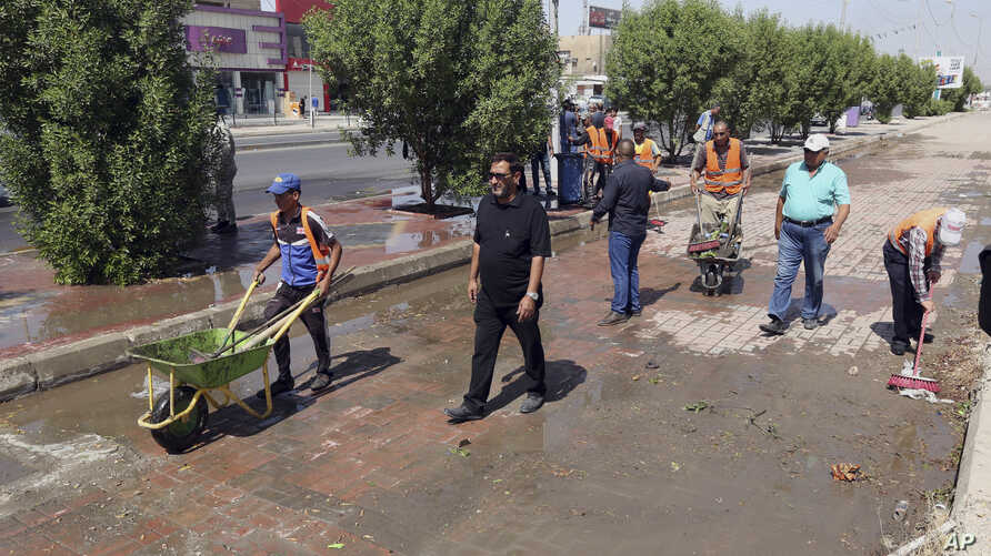 Iraqi municipality workers clean the scene of a suicide attack in Baghdad's western Eskan neighborhood, Iraq, Sunday, Sept. 25, 2016. A suicide bomber killed several people who were setting up tents on Sunday ahead of a major Shi'ite religious observ