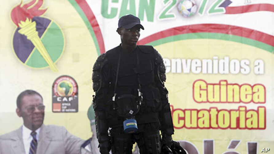 """A member of Equatorial Guinea's police special forces stands in front of a banner of President Teodoro Obiang Nguema Mbasogo outside Estadio de Bata """"Bata Stadium"""", which will host the opening match and ceremony for the African Nations Cup, in Bata J"""
