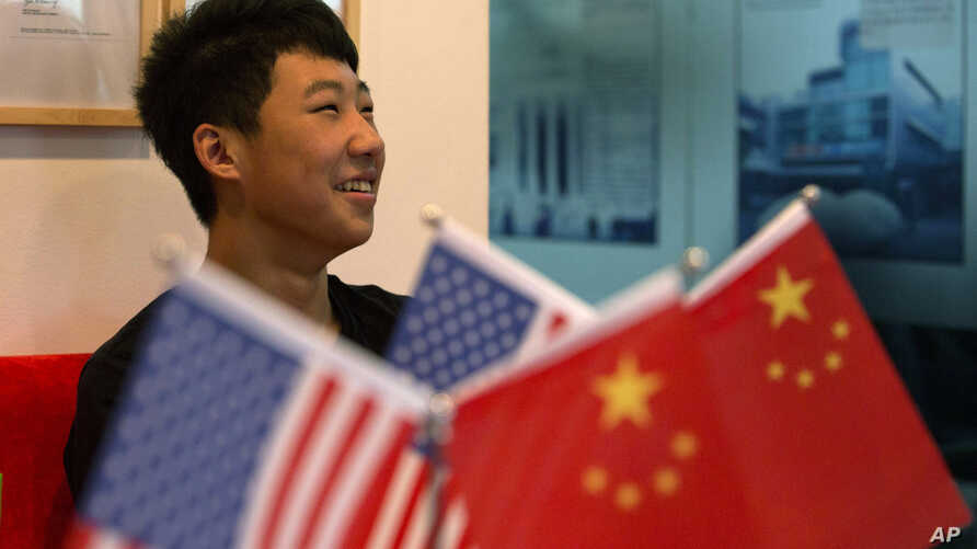 FILE - 16-year-old Zhang Kaisheng smiles near Chinese and U.S. national flags at the lobby of Focus Education, a tutoring and consulting agency in Beijing.