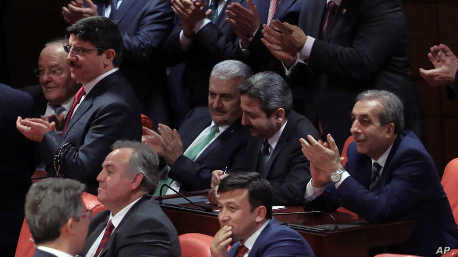 Binali Yildirim, center left, Turkey's current transportation minister, who was tapped by the ruling party as candidate of choice as the country's next prime minister, applauds with legislators after the vote on a constitutional amendment on parliame