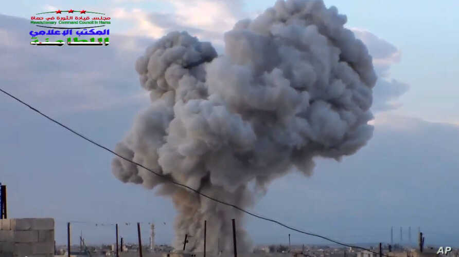 This image taken from video provided by the Syrian activist-based media group Syrian Revolutionary Command Council in Hama, which has-been verified and is consistent with other AP reporting, shows smoke rising after a Russian airstrike hit buildings