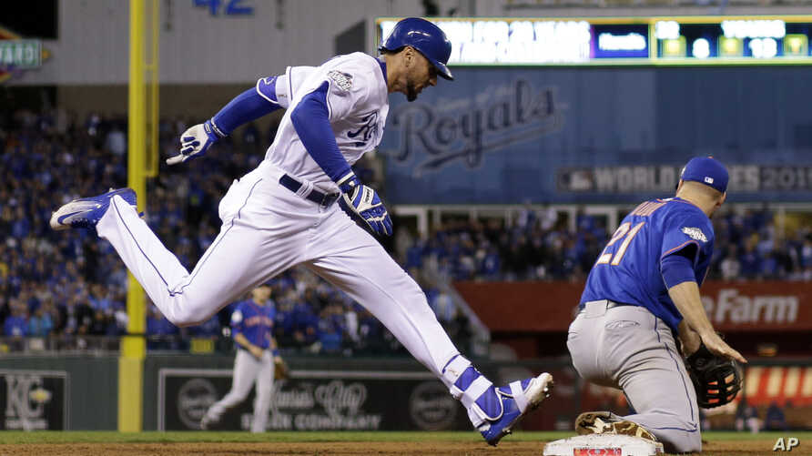 Kansas City Royals' Paulo Orlando beats the throw to first taken by New York Mets' Lucas Duda (21) during the 12th inning of Game 1 of the Major League Baseball World Series, Oct. 27, 2015, in Kansas City, Mo.