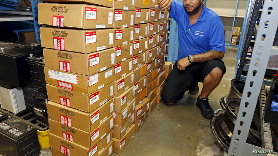 FILE - Parts department worker Frank Jorge stands next to boxes containing recalled Takata air bag inflators that were removed at the AutoNation Honda dealership in Miami, Florida, June 25, 2015.