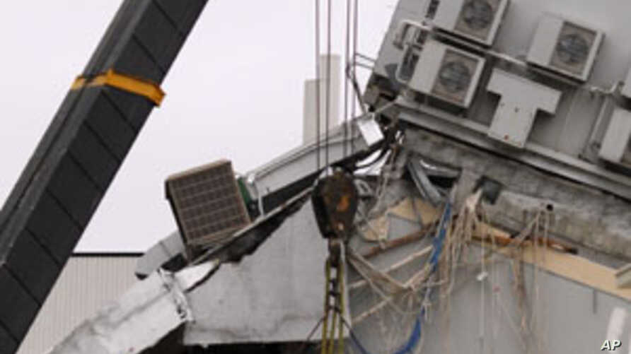 Emergency workers are lifted into the remains of the Pyne Gould Guinness building, which was destroyed following earthquake, in the southern New Zealand city of Christchurch, February 23, 2011