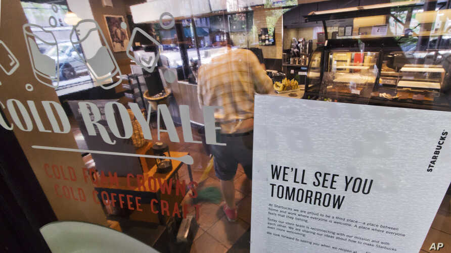A sign advising that a Starbucks is closed, is posted in the window of a store on New York's West Side as a barista mops the floor, May 29, 2018.