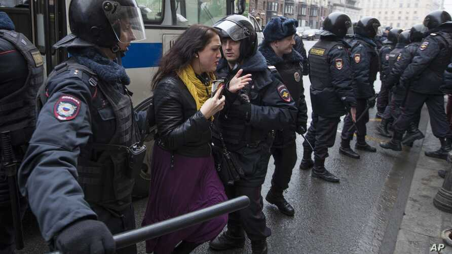 Police officers try to detain a woman in the main street in Moscow, April 2, 2017.