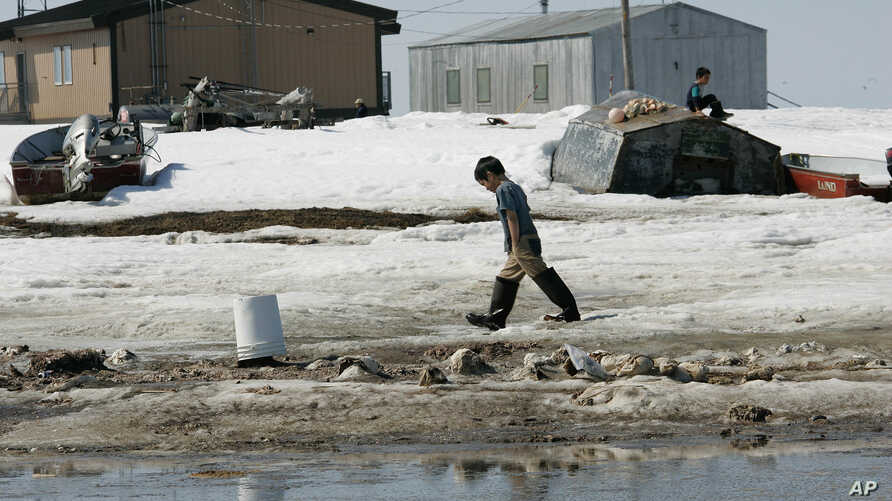 A young boy walks along the frozen banks of the Newtok River, in Newtok, Alaska Wednesday, May 24, 2006, past frozen human waste dumped because the village lacks indoor plumbing.