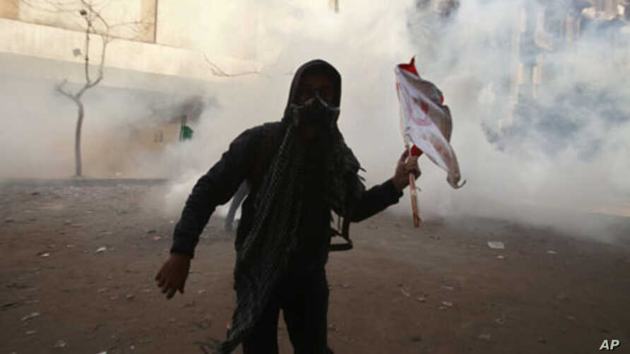A protester runs away from tear gas during clashes with security forces near the Interior Ministry in Cairo, February 4, 2012.