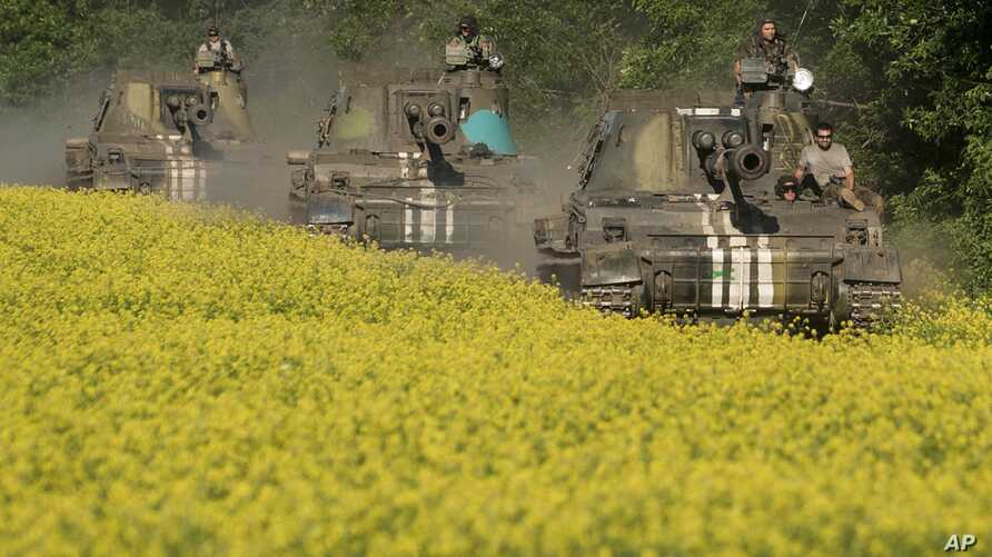 FILE - Ukrainian self-propelled artillery vehicles make their way to positions near Donetsk, eastern Ukraine, June 7, 2015. A new report says some Ukrainian artillery united were tracked by Russian hackers from late 2014 through 2016.