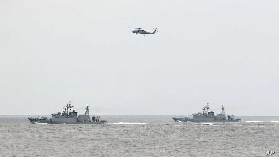 A Taiwan Navy helicopter flies over two Taiwan made corvettes during a navy exercise in the bound of Suao naval station in Yilan County, northeast of Taiwan, Apr. 13, 2018.