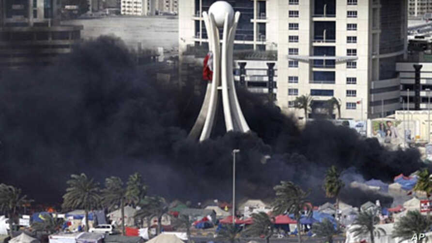 Black smoke billows from burning tents in Pearl Square in Bahraini capital Manama on March 16, 2011