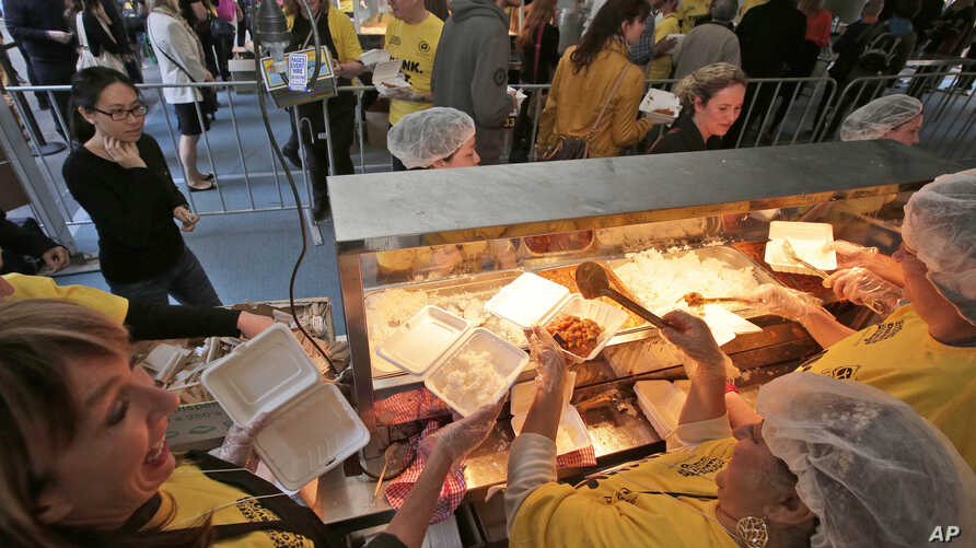 FILE - Volunteers hand out free meals made from rescued ingredients organized by the charity organization Oz Harvest in Sydney's central business district, July 29, 2013. The organizers goal is to feed 5,000 people over a lunch period in a bid to rai