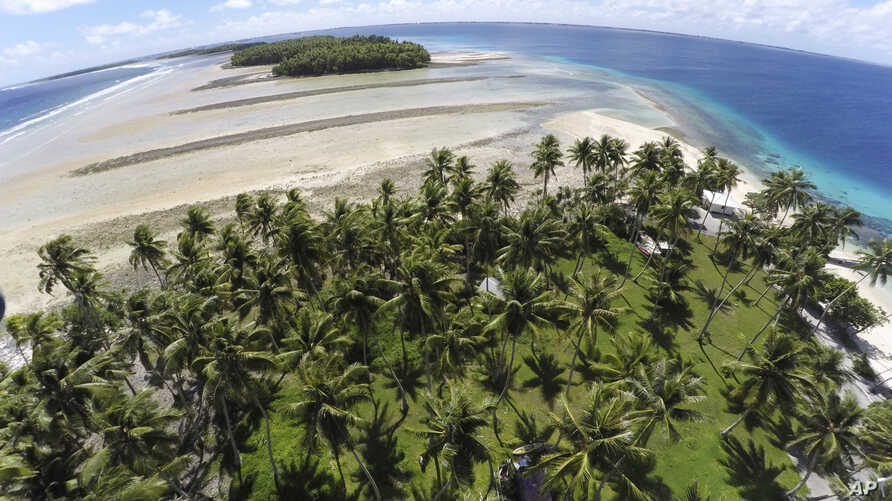 FILE - This Nov. 6, 2015, photo shows a large section of land between the trees washed away due to continuing rising sea leaves on Majuro Atoll, Marshall.