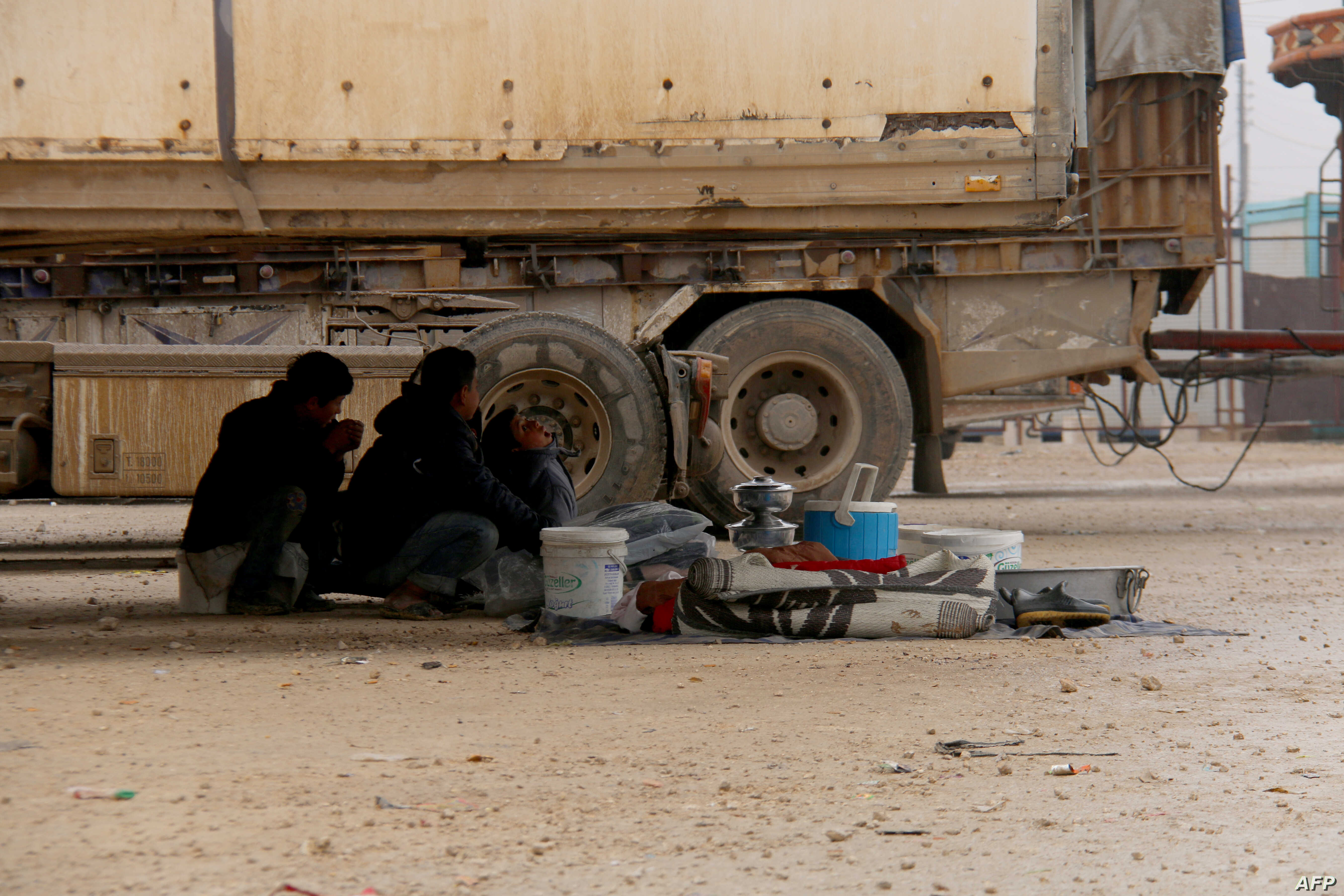 Displaced Syrians fleeing areas in the northern embattled province of Aleppo, sit under a truck at the Bab al-Salama camp, set up outside the Syrian city of Azaz on Syria's northern border with Turkey, Feb. 12, 2016.