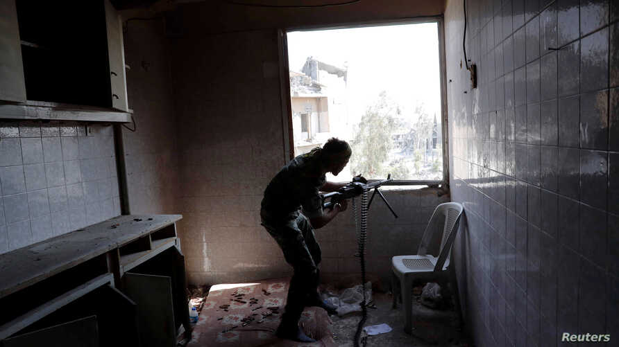 A fighter of Syrian Democratic Forces takes up position inside a building during a battle with Islamic State militants at the frontline in Raqqa, Syria, Oct. 7, 2017.