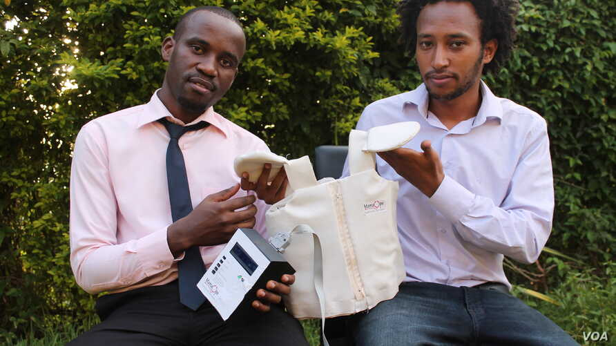 Makerere University Telecom graduates Brian Turyabagye (left) and Besufekad Shifferaw (Right) show off the smart jacket that will be used in the diagnosis of Pneumonia in children, Kampala, Uganda, April 5, 2017. (H. Althumani/VOA)