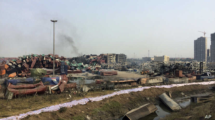 FILE - Smoke rises from damaged container boxes near the site of an explosion at a warehouse in northeastern China's Tianjin municipality, Aug. 17, 2015.